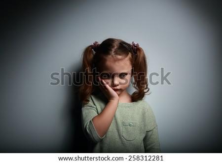 Sad alone kid girl thinking on dark background. Problems at family. - stock photo