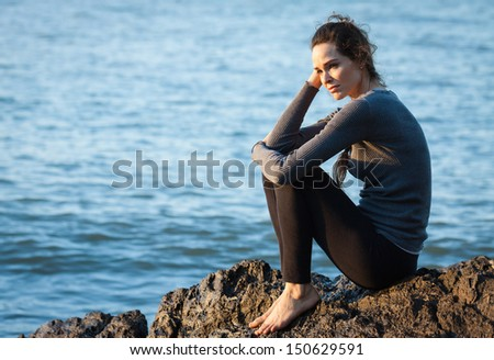 Sad and depressed woman sitting by the ocean - stock photo