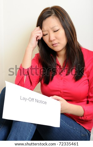 Sad and depressed young Asian woman sitting on floor against wall holding Lay-off notice in her hand. - stock photo