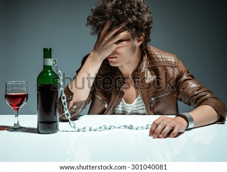 Sad and depressed young man in alcohol addiction / photo of youth addicted to alcohol, alcoholism concept, social problem - stock photo