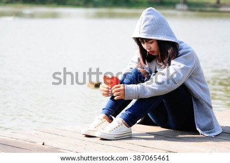 Sad and disappointed woman sits near river - stock photo