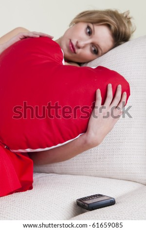 Sad and disappointed woman waiting a call, embracing a heart shaped  cushion