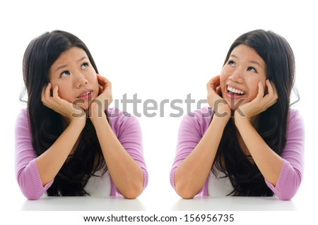 Sad and happy face expression of Asian woman, hands holding face sitting isolated over white background. - stock photo