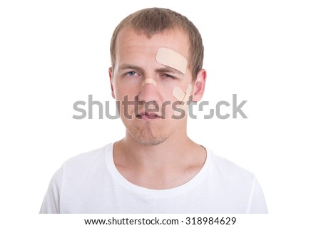 sad and injured young man with adhesive plaster on his face - stock photo
