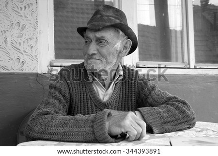 Sad and lonely old man sitting alone - stock photo