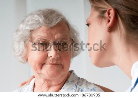 Sad and lonely senior woman with nurse - stock photo