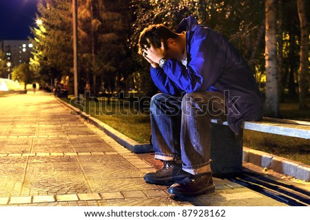 sad and lonely teenager with hidden face sitting in the night park - stock photo