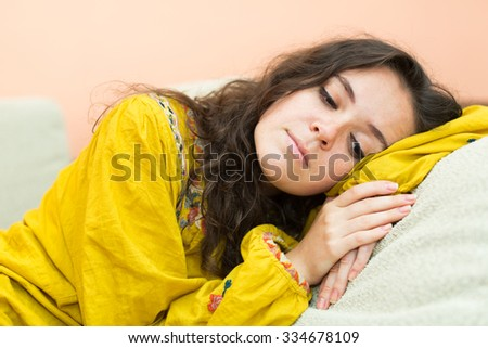 sad and lonely  woman lying on  sofa at home - stock photo