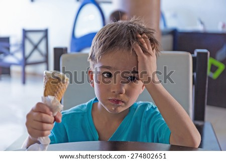 sad and pensive child with ice cream in hand - stock photo