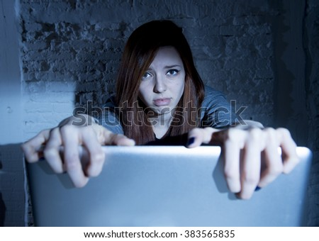 sad and scared female teenager with computer laptop suffering cyberbullying and harassment being online abused by stalker or gossip feeling desperate and humiliated in cyber bullying concept - stock photo