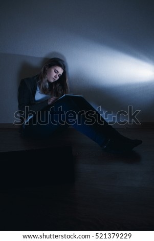 sad and scared female teenager with tablet computer and laptop suffering cyberbullying and harassment being online abused by stalker or gossip feeling desperate and humiliated in cyber bullying