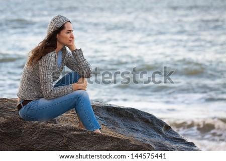 Sad and thoughtful woman sitting by the water deep in thought. - stock photo
