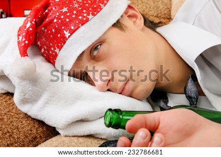 Sad and Tired Teenager with Bottle of the Beer and Santa Hat on the Sofa at the Home - stock photo