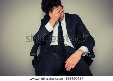 Sad and tired young businessman sitting in an office chair - stock photo
