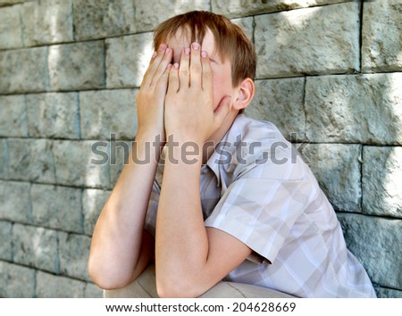 Sad and Troubled Kid sitting by the Wall - stock photo