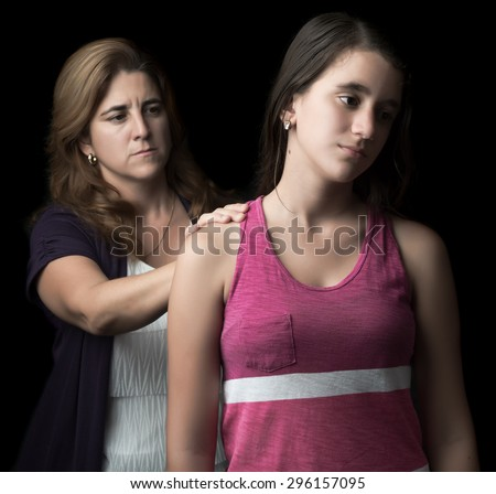 Sad and troubled teenage girl with her mother trying to comfort her isolated on black - stock photo