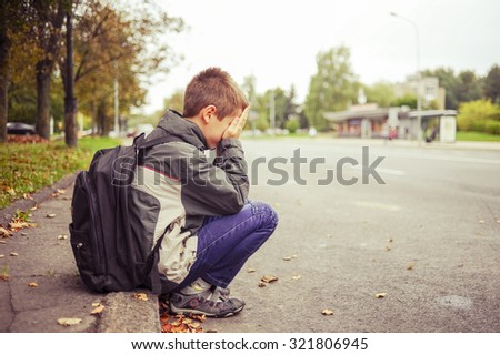sad and unhappy child in the street - stock photo