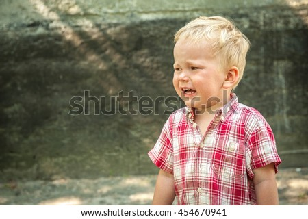 sad and unhappy child in the street. Upset problem child with head in hands sitting on staircase concept for bullying, depression stress or frustration. concrete wall as  background - stock photo