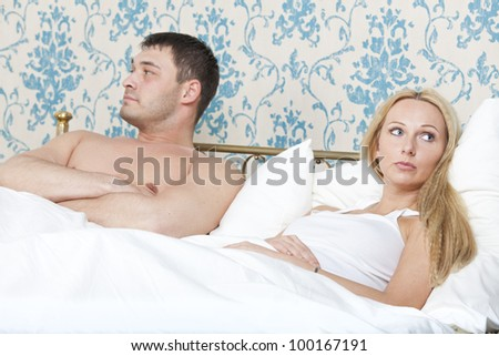 sad and unhappy couple lying in bed - stock photo