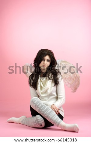 Sad angel sitting on the floor against pink background - stock photo