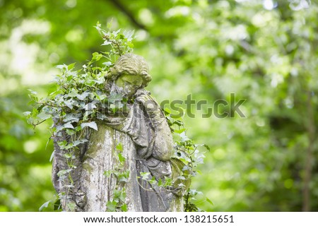 Sad angel statue on old cemetery - stock photo