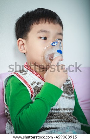 Sad asian child holds a mask vapor inhaler for treatment of asthma on sickbed in hospital. Breathing through a steam nebulizer. Concept of inhalation therapy apparatus. Vignette style. - stock photo