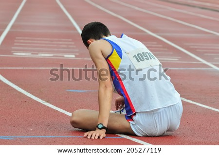 Sad athlete on the ground after loosing race - stock photo