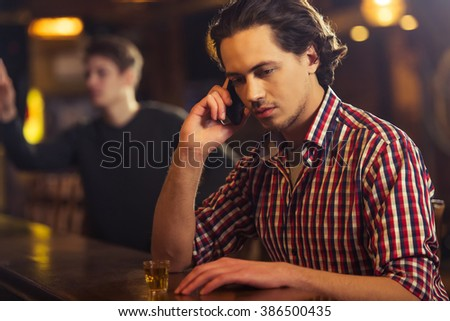 Sad attractive man in casual clothes is talking on the mobile phone while sitting at bar counter in pub - stock photo