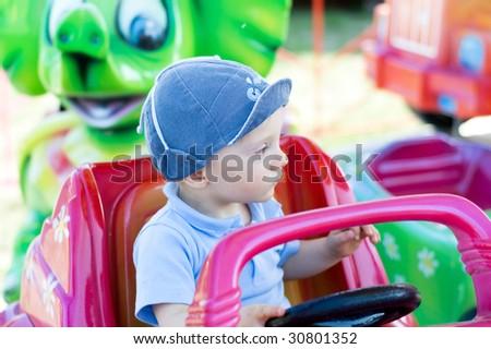Sad baby boy on merry go round - stock photo