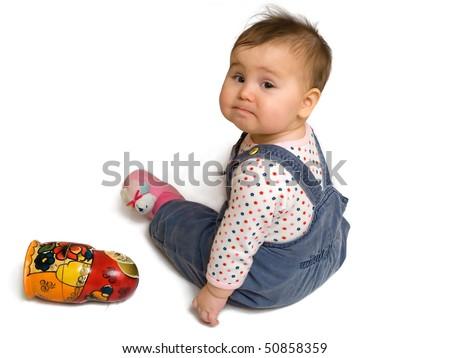 Sad baby boy sitting on white and matreshka toy - stock photo