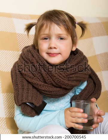 Sad baby girl in warm scarf with glass - stock photo