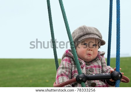 Sad baby girl on a swing - stock photo