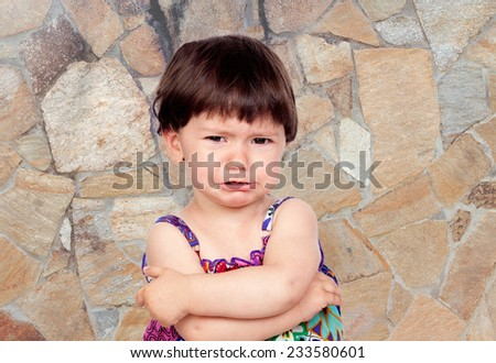 Sad baby girl with a stone wall of background - stock photo
