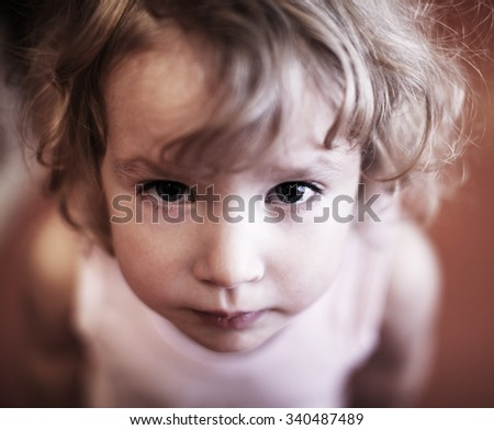 Sad baby. Grief little girl looking up