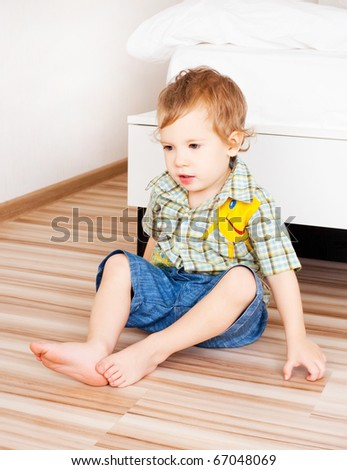 sad baby sitting on the floor at home - stock photo