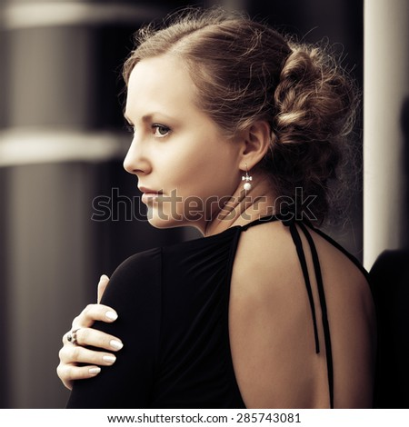 Sad beautiful fashion woman standing at the wall - stock photo