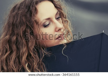 Sad beautiful fashion woman with umbrella - stock photo