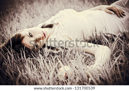 Sad beautiful girl lying on a grass. Faded effect - stock photo