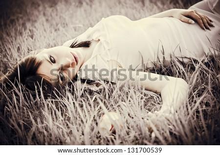 Sad beautiful girl lying on a grass. Faded effect - stock photo