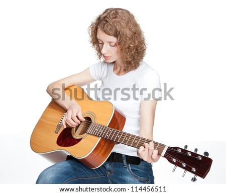 Sad beautiful girl playing on guitar on white background