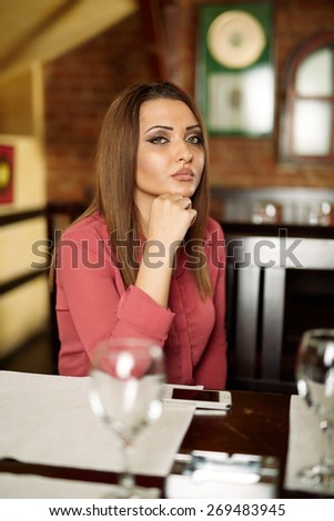 Sad beautiful lady sitting in a restaurant and thinking away - stock photo