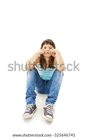 Sad beautiful little girl, sitting. Isolated on white background. - stock photo