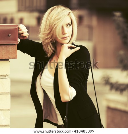 Sad beautiful woman fashion on city street. Female fashion model in black jacket outdoor - stock photo