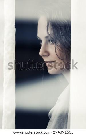Sad beautiful woman looking out window - stock photo