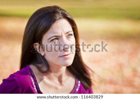 Sad beautiful woman outdoors against fall leaf background - stock photo