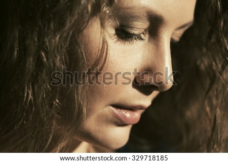 Sad beautiful woman with long curly hairs looking down - stock photo