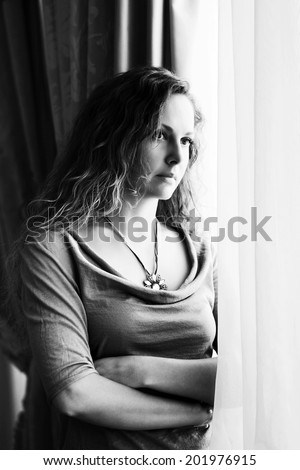 Sad beautiful woman with long curly hairs looking out window  - stock photo