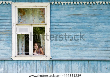 Sad bored little girl looking out the country house window leaning her face on her hand. Outside view - stock photo