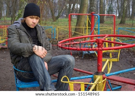 Sad boy at a old abandoned playground - stock photo