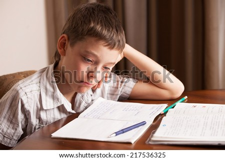 Sad boy doing homework. Child education - stock photo